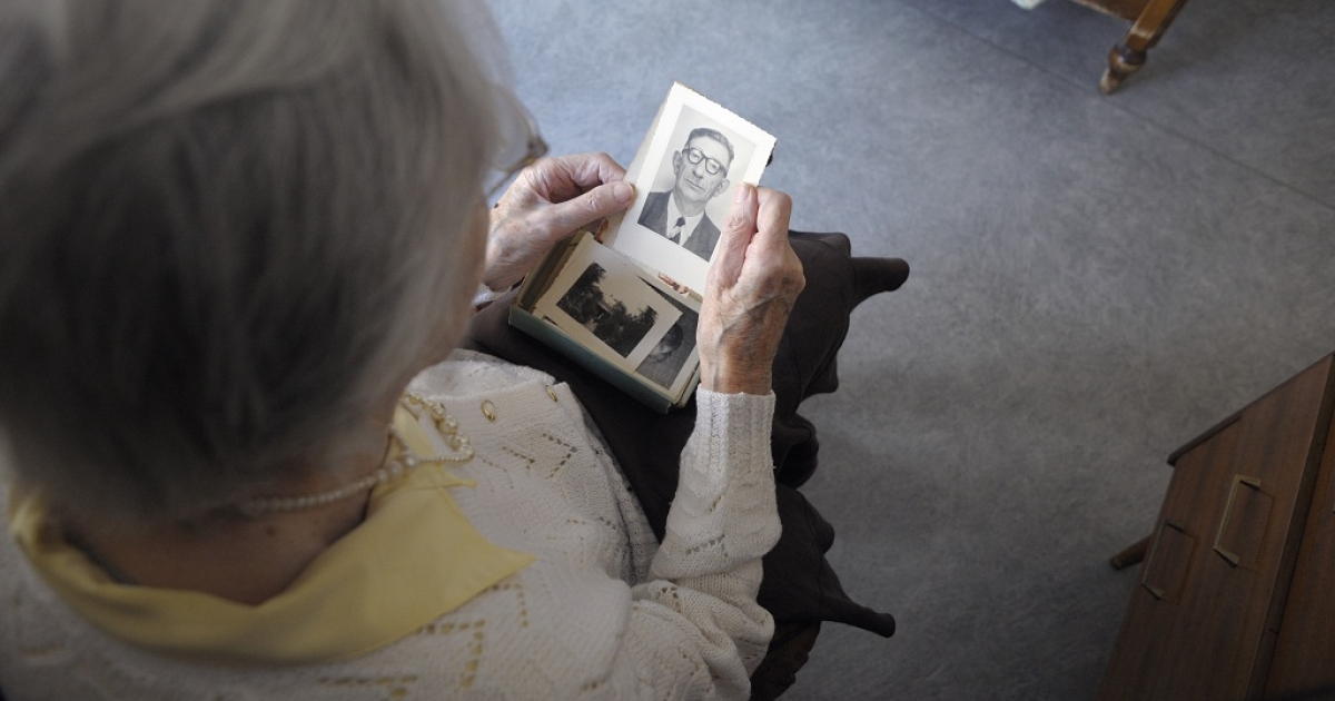 A woman suffering from Alzheimer's looks at an old photo. Scientists believe they have found one indicator of Alzheimer's in women.</p>