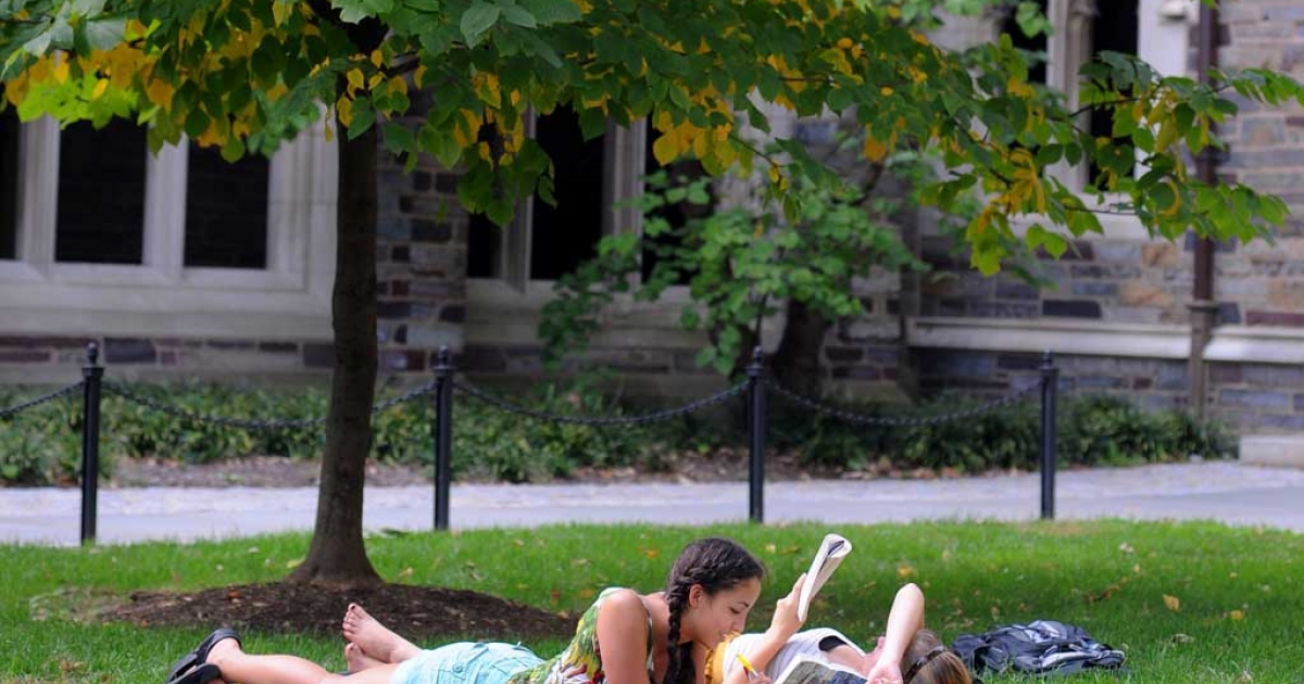 Claudia Kelley (L), of San Francisco, California and Cameron Langford of Davidson, North Carolina lay on the grass and read in a courtyard at Princeton University in Princeton, New Jersey.</p>