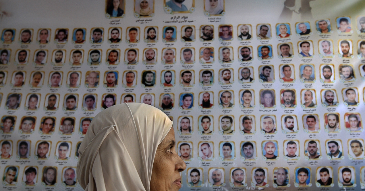 A Palestinian woman looks at a banner bearing names and photos of Palestinian prisoners held in Israeli jails in front of the International Red Cross building in East Jerusalem. Oct. 12, 2011.</p>