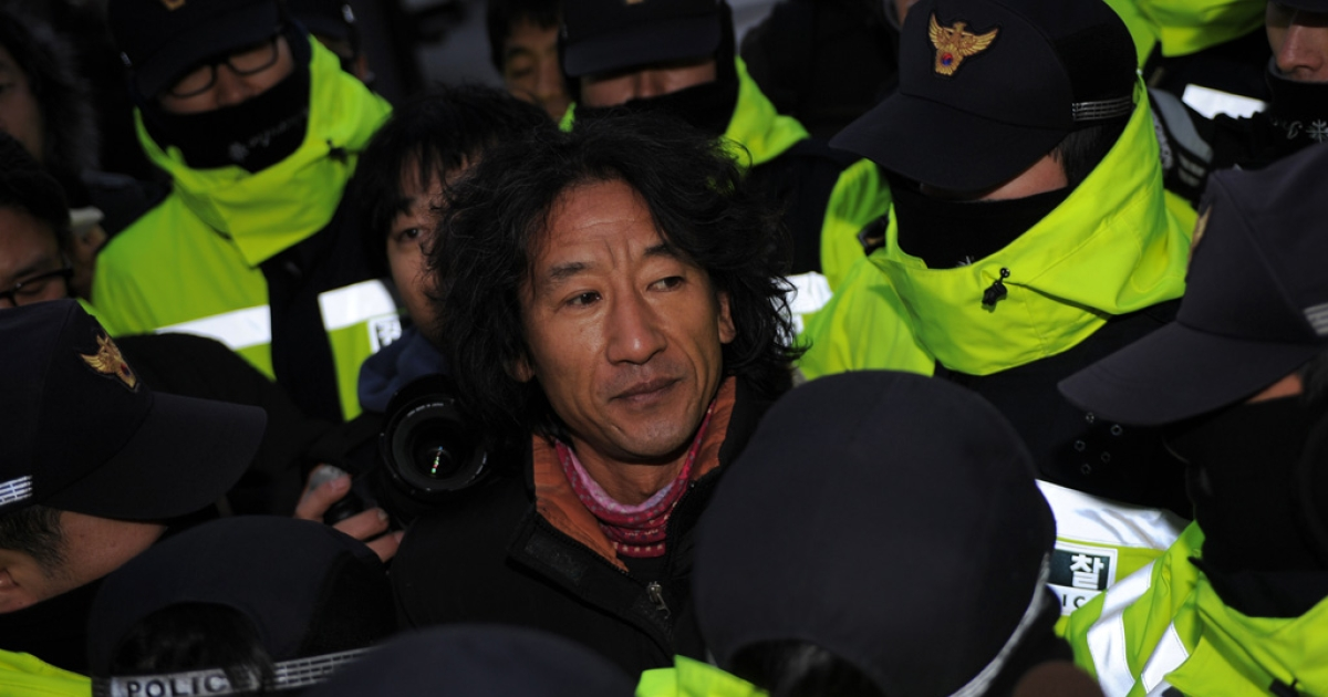 An pro-North Korean activist is surrounded by Seoul policemen before showing his respect to the death of North Korean leader Kim Jong Il on Dec. 26, 2011.</p>