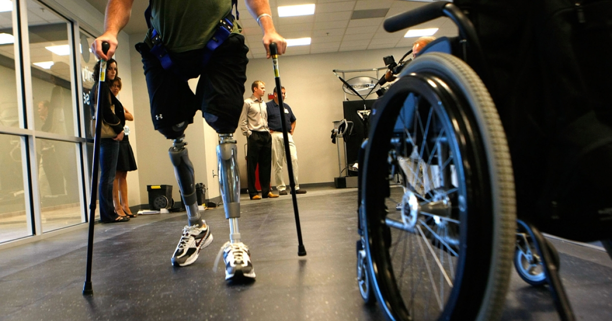 A Marine walks with prosthetic limbs at the Walter Reed Army Medical Center. Researchers have moved one step closer to being able to fuse nerves with prosthetic limbs, a move which would give amputees finer control over their artificial limbs.</p>