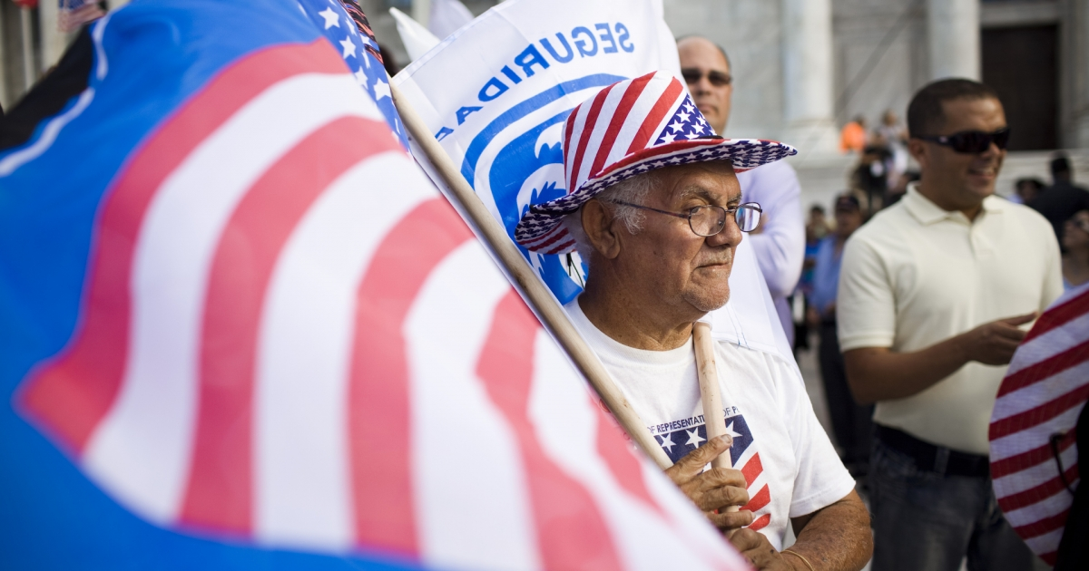 Roberto Maldonado, 75, sells flags at a New Progressive Party rally where Mitt Romney was campaigning Friday on the North Side of the Capitol building in San Juan, Puerto Rico.</p>
