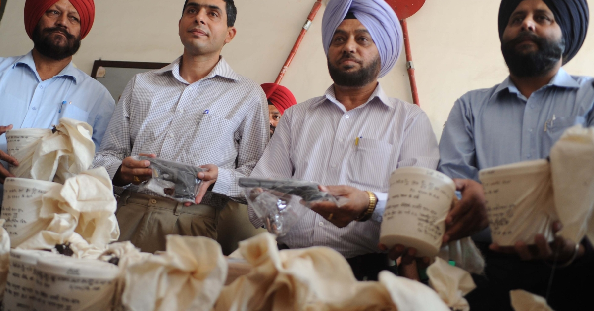 India's Punjab state Special Narcotics Cell police officials display 20 kg of heroin, two pistols and 12 lakhs ($23,000) recovered from alleged smugglers, April 21, 2012.</p>