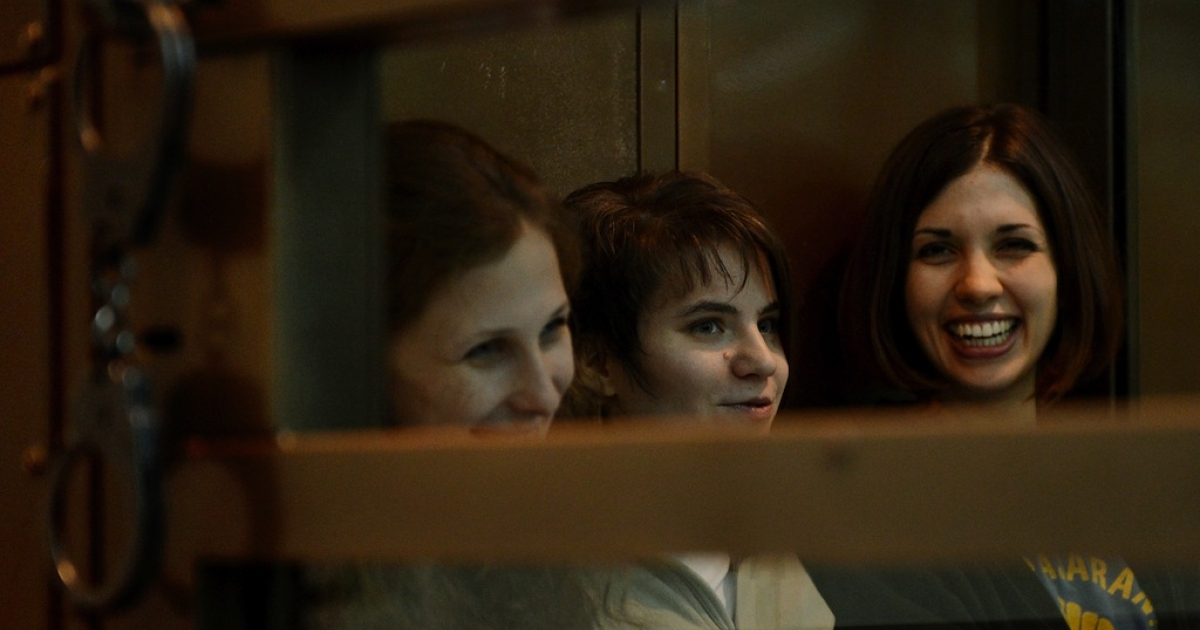 Members of the all-girl punk protest band 'Pussy Riot' (L-R) Yekaterina Samutsevich, Maria Alyokhina and Nadezhda Tolokonnikova, sit in a glass-walled cage in Moscow, on Oct. 1, 2012.</p>