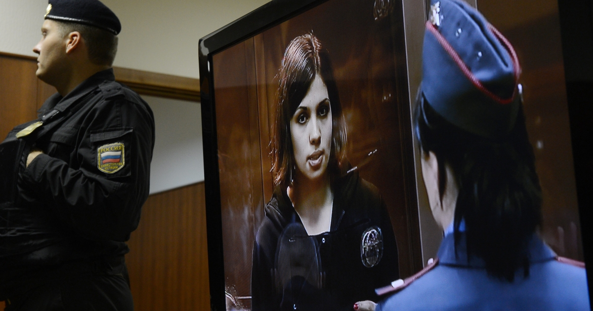 A police officer near a screen showing Pussy Riot member Nadezhda Tolokonnikova in court on Wednesday. The case reflects the Kremlin's mounting exercise of arbitrary power.</p>