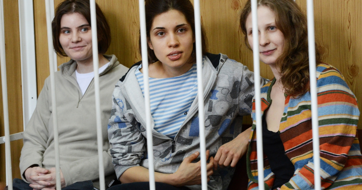 Members of the all-girl punk band 'Pussy Riot,' Nadezhda Tolokonnikova (C), Maria Alyokhina (R) and Yekaterina Samutsevich (L), sit behind bars during a court hearing in Moscow on July 20, 2012.</p>