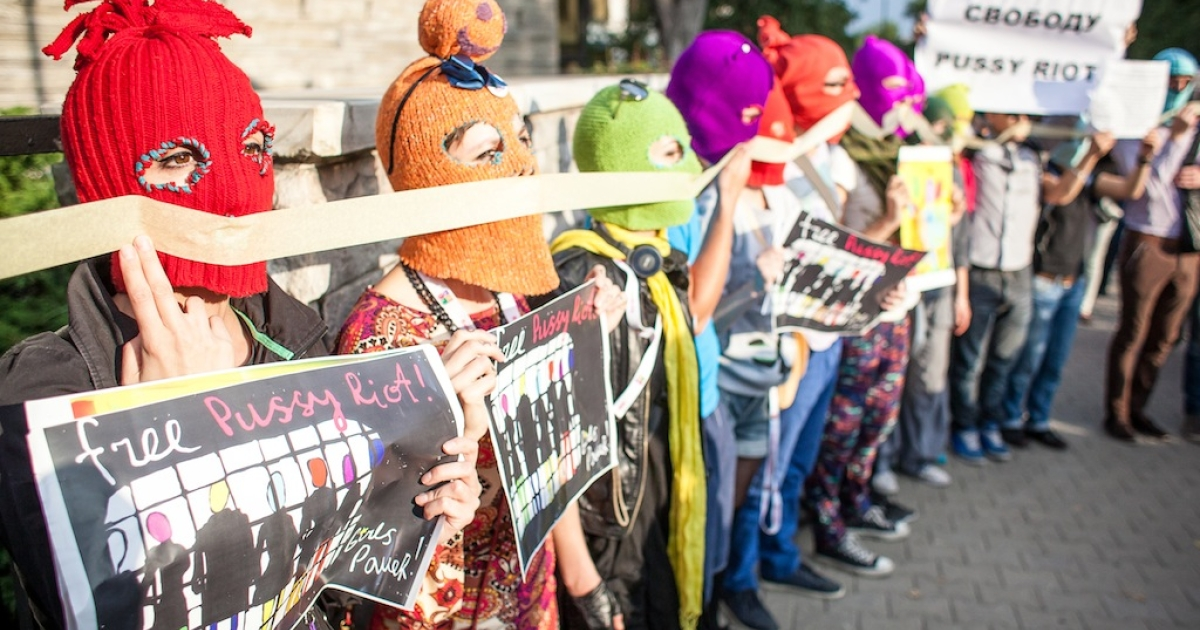 Supporters of the Russian punk band 'Pussy Riot' wear masks and hold placards demanding their freedom as they protest in front of of the Russian embassy in Warsaw on August 17, 2012.</p>