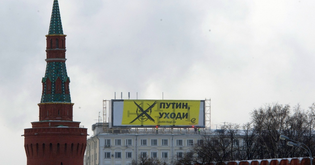 Opposition activists hang their banner reading: 'Putin, leave!' atop a bulding's roof, just over the Moskva River river from the Kremlin (foreground) in Moscow, on February 1, 2012</p>