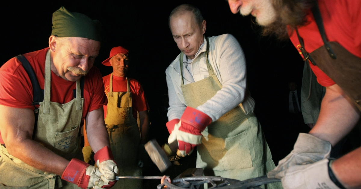 Russia's Prime Minister Vladimir Putin (C) strikes iron as he visits