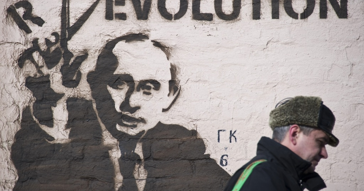 In Moscow on March 3, 2012, a man walks past a wall painted with graffiti, featuring Russia's Prime Minister and presidential candidate, Vladimir Putin. Tomorrow, voters will likely send Putin back to the Kremlin for his third presidential term.</p>