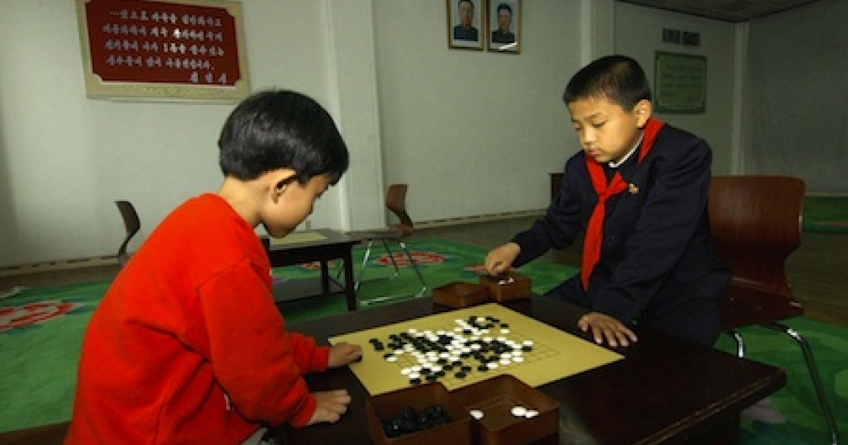 North Korean students play a game of 'go' during their class at the Mangyondae school children's palace in Pyongyang, North Korea, as portraits of North Korean leader Kim Jong-Il (top R) and his late father Kim Il-Sung (top-L) look down from the walls.</p>