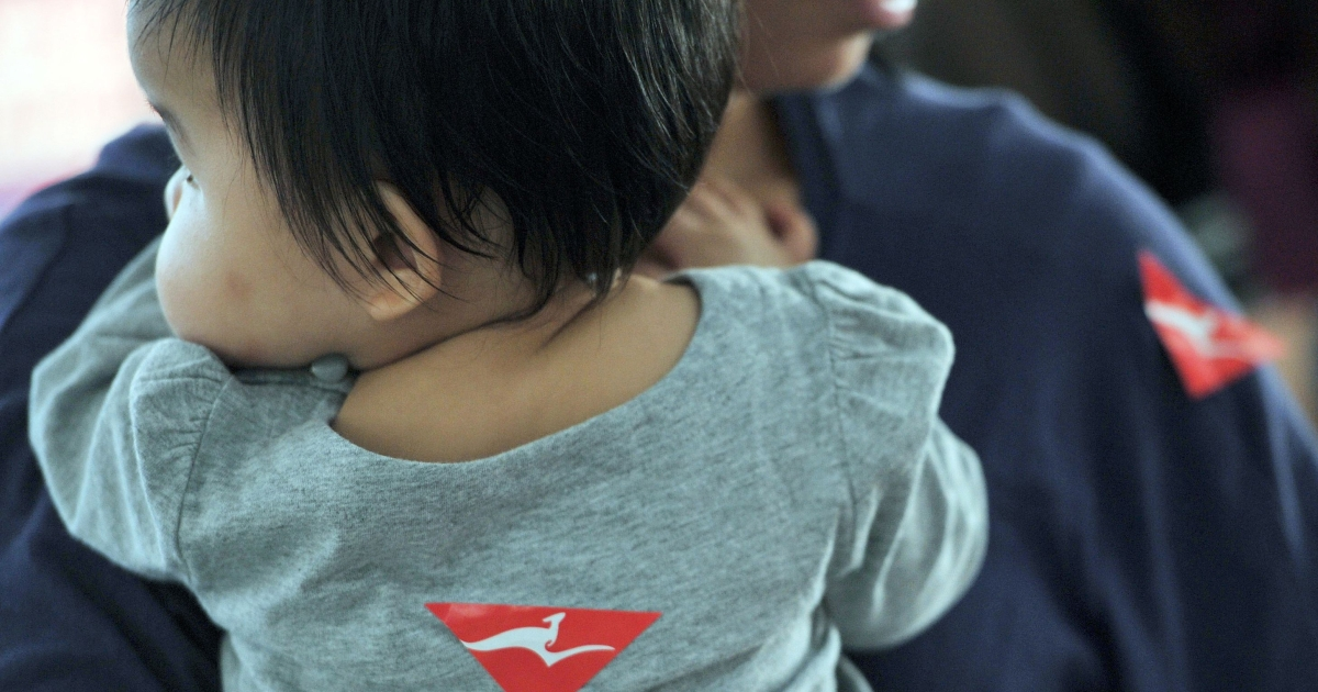 A Qantas airline sticker is seen on a toddler and her caretaker at Hong Kong international Airport on November 1, 2011.</p>