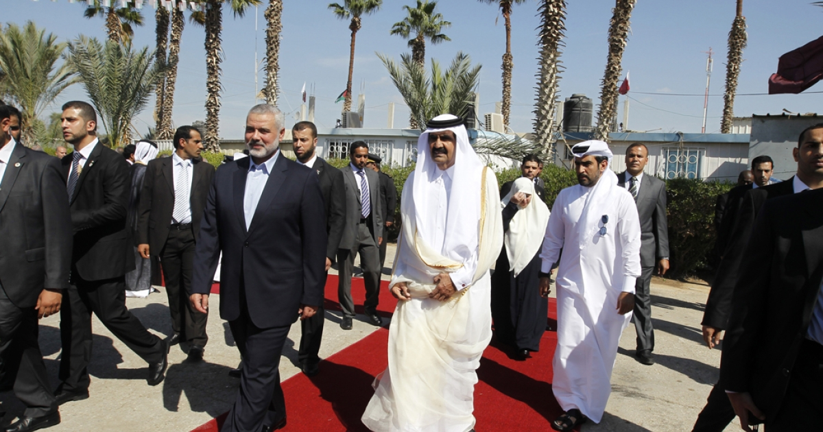 Qatari Emir  Sheikh Hamad bin Khalifa al-Thani (C-R) walks alongside Gaza's Hamas prime minister Ismail Haniyeh (C-L) during a welcome ceremony at the Rafah border crossing with Egypt  on October 23, 2012 in the Gaza Strip.</p>