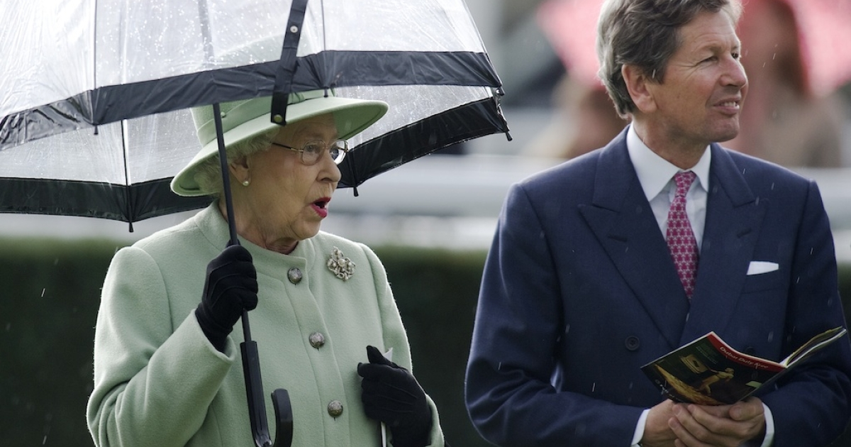 The Queen shelters from the rain with racing manager John Warren at Newbury racecourse on April 21, 2012 in Newbury, England.</p>