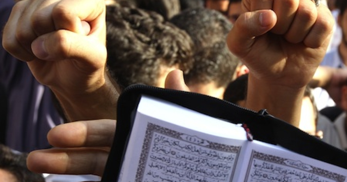 Iranian men clench their fists as they hold an open copy of the Muslim holy book, the Quran, during a protest against the earlier threats by a US pastor, Terry Jones, to burn a copy of the holy book.</p>
