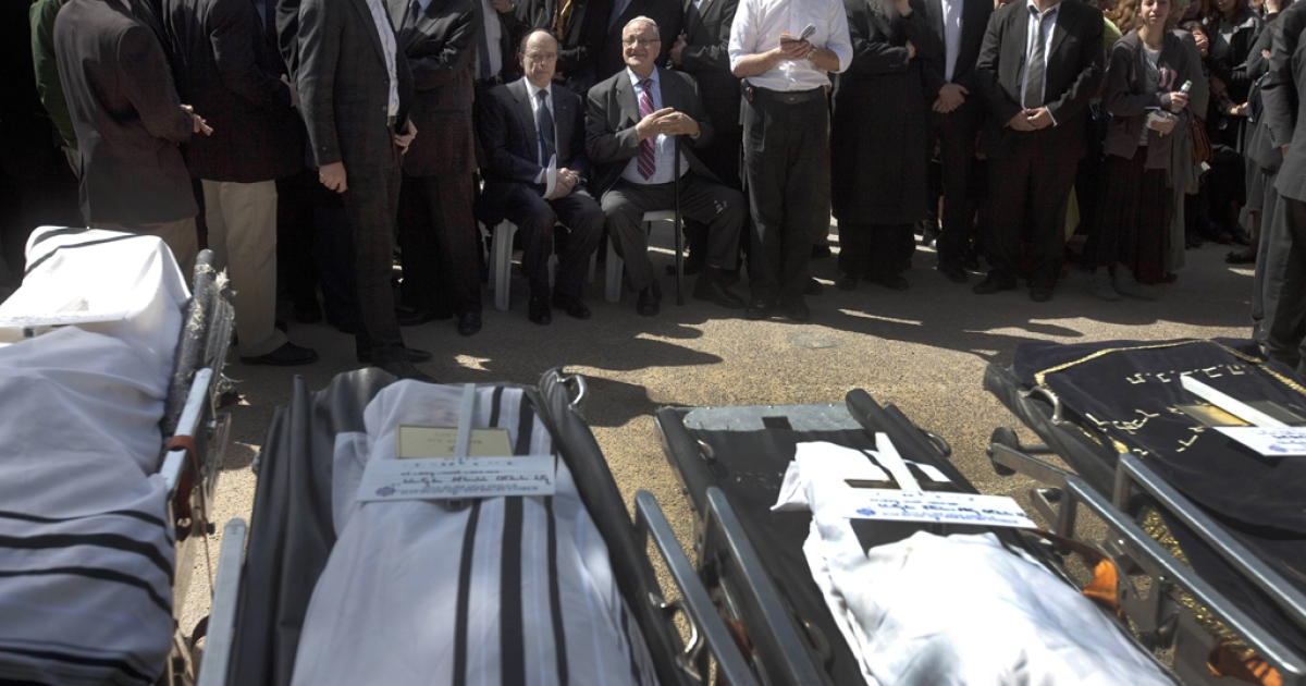 French Foreign Minister Alain Juppe sits (C-L) next to mourners in front of the bodies of teacher Jonathan Sandler (L), and his children Gabriel 4, Arieh 5, and Miriam Monsonego 7 (R) victims of Toulouse school shooting, during their funeral in Jerusalem on March 21, 2012.</p>