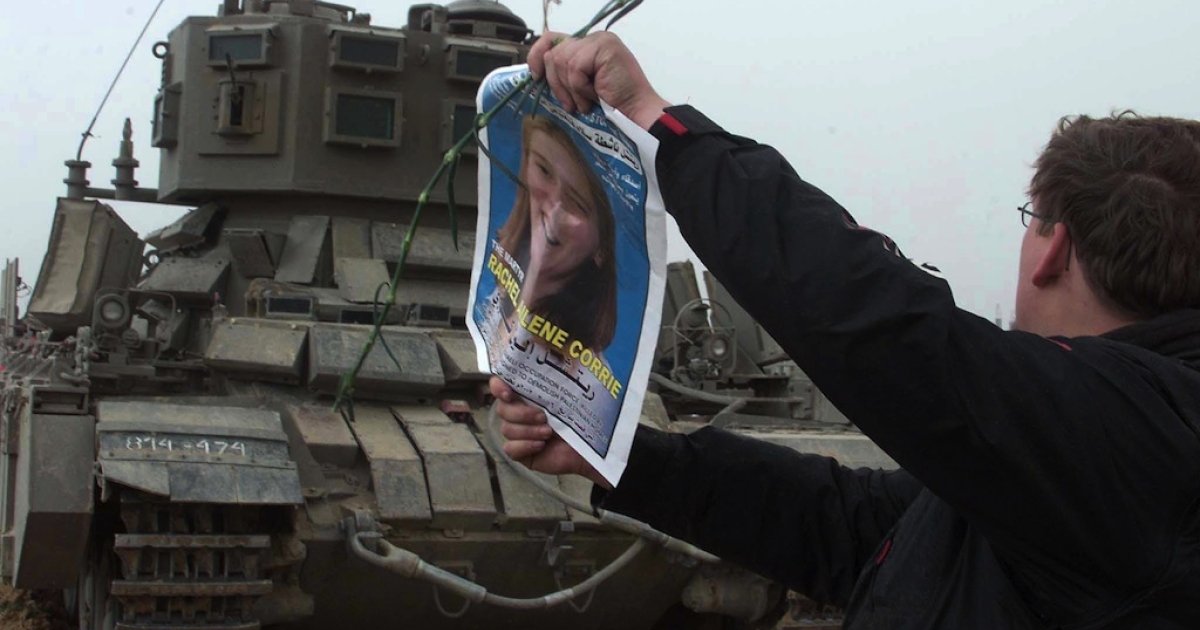 A member of the International Solidarity Movement waves a picture of Rachel Corrie in front of an Israeli tank during a demonstration where Corrie was killed on March 18, 2003. ISM members and Palestinians protested the killing of Corrie who was crushed to death 16 March by an Israeli army bulldozer in Rafah as she and other activists tried to prevent the destruction of Palestinian homes, Palestinian officials and a US witness said.</p>