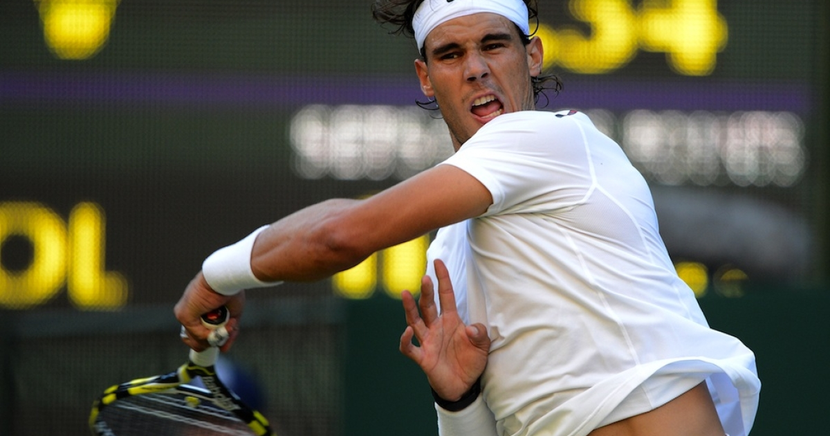 Rafael Nadal plays a forehand shot during his second round match against Lukas Rosol at Wimbledon on June 28, 2012.</p>