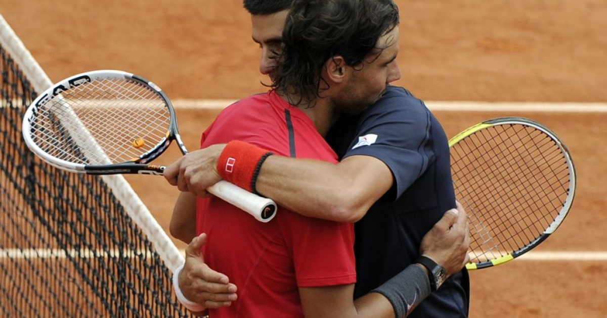 Rafael Nadal (L) hugs Novak Djokovic, who he beat in four sets to win the 2012 French Open.</p>