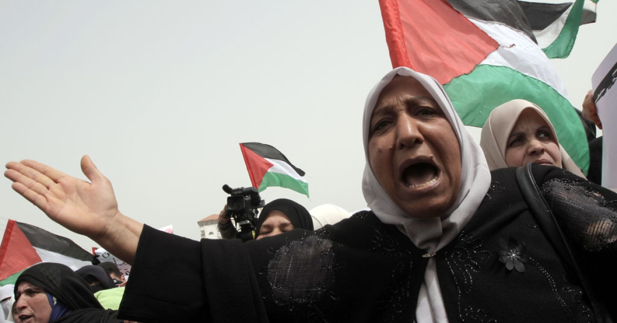 Palestinian women wave their national flag and shout slogans during a protest near the Rafah border crossing with Egypt in the southern Gaza Strip on March 20, 2012.</p>