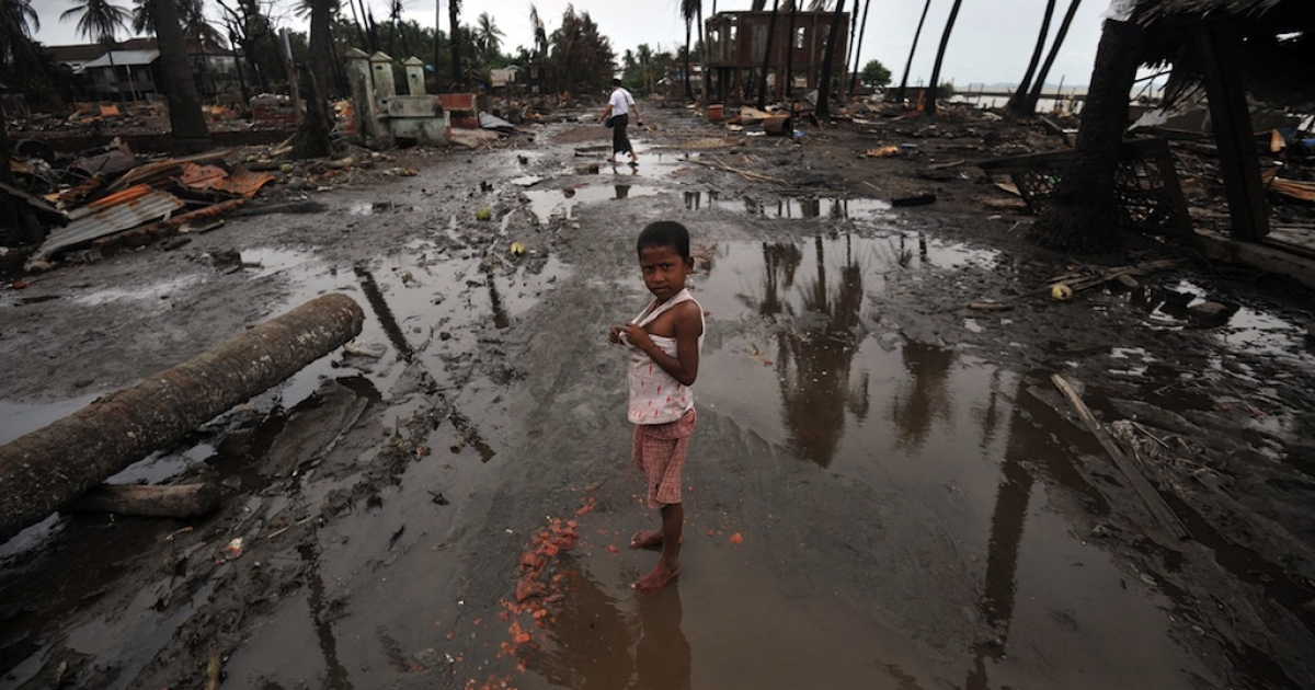 A child stands in a street lined with destroyed buildings following days of sectarian violence in Myanmar's western state of Rakhine on June 16, 2012. Tens of thousands have been displaced and 73 people killed in the region since May.</p>