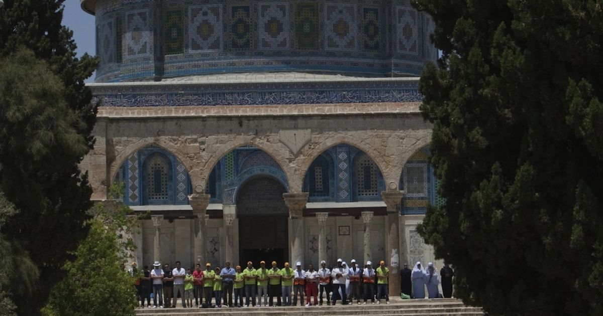 Palestinian worshippers pray outside the Dome of the Rock at the Al-Aqsa Mosque compound in Jerusalem during the first Friday prayers of the Muslim holy month of Ramadan on July 20, 2012.</p>