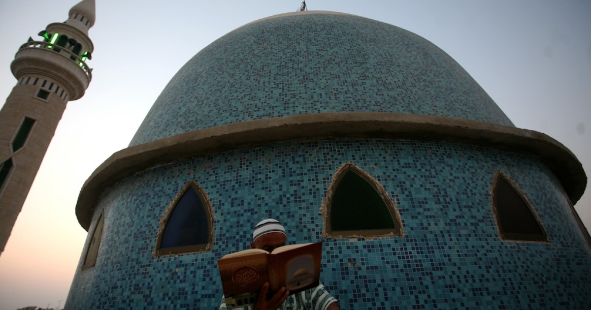 A Palestinian man reads the Quran outside a mosque in the West Bank city of Jenin on the first day of the Muslim holy fasting month of Ramadan on July 20, 2012.</p>