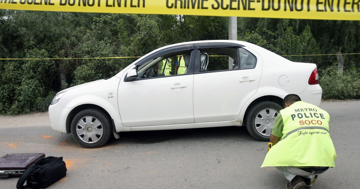 Nepalese crime officers examine the car in which Supreme Court Judge Rana Bahadur Bam was shot dead in Kathmandu on May 31, 2012.</p>