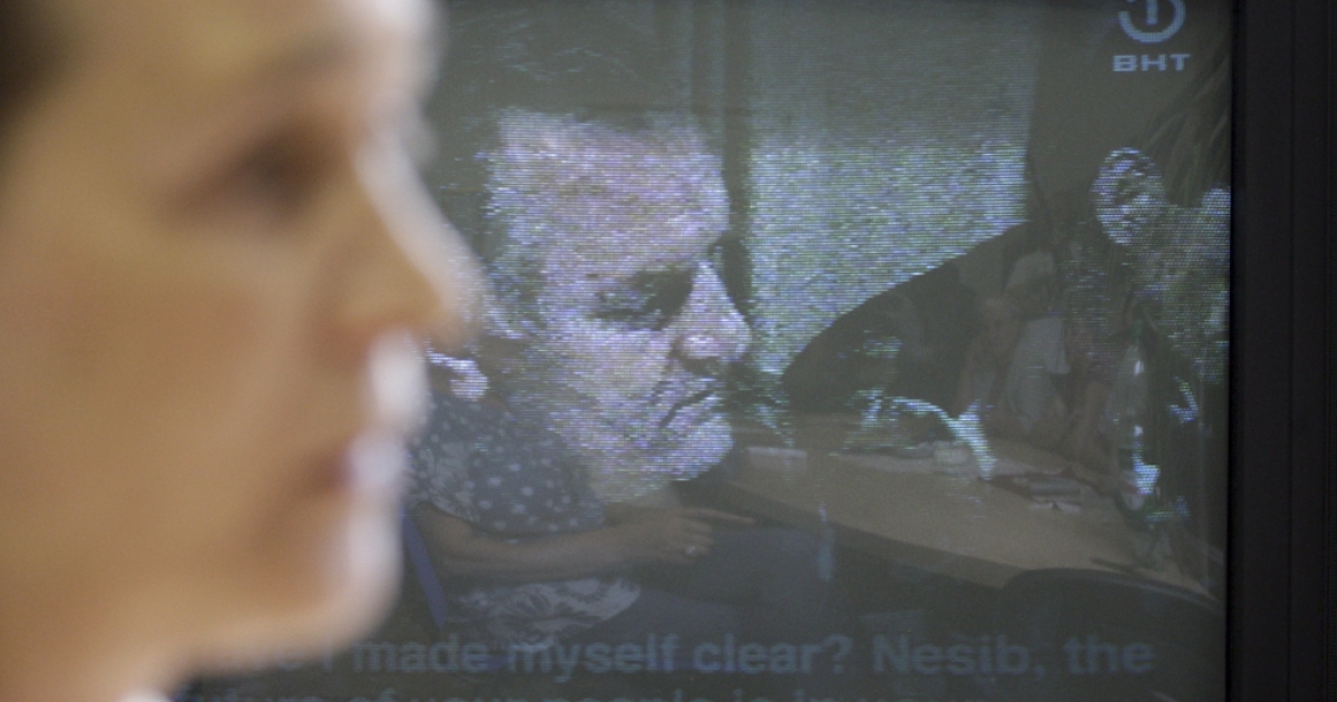 A Bosnian Muslim woman, survivor of the 1995 Srebrenica massacre, Sabaheta Fejzic, watches the news on the arrest of Ratko Mladic (on tv screen) in Sarajevo, on May 26, 2011. Ratko Mladic, who was arrested Thursday after almost 16 years on the run, was the Bosnian Serb army commander whose brutish leadership is blamed for the worst atrocities in Europe since World War II. Mladic, 69 not only ordered and masterminded the Srebrenica massacre of 8,000 Muslim men and boys but also the 44-month siege of Sarajevo which cost an estimated 10,000 lives.</p>