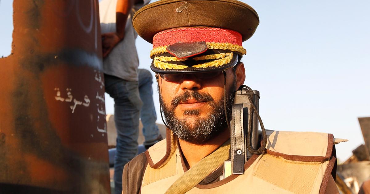 A Libyan rebel poses with a hat belonging to Muammar Gaddafi at Bab Al-Aziziya compound in Tripoli August 23, 2011.</p>