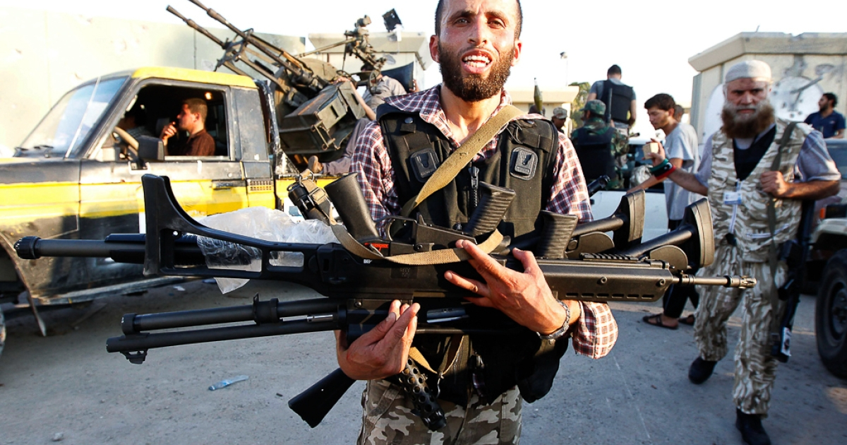 A Libyan rebel holds weapons at Bab Al-Aziziya compound in Tripoli August 23, 2011.</p>