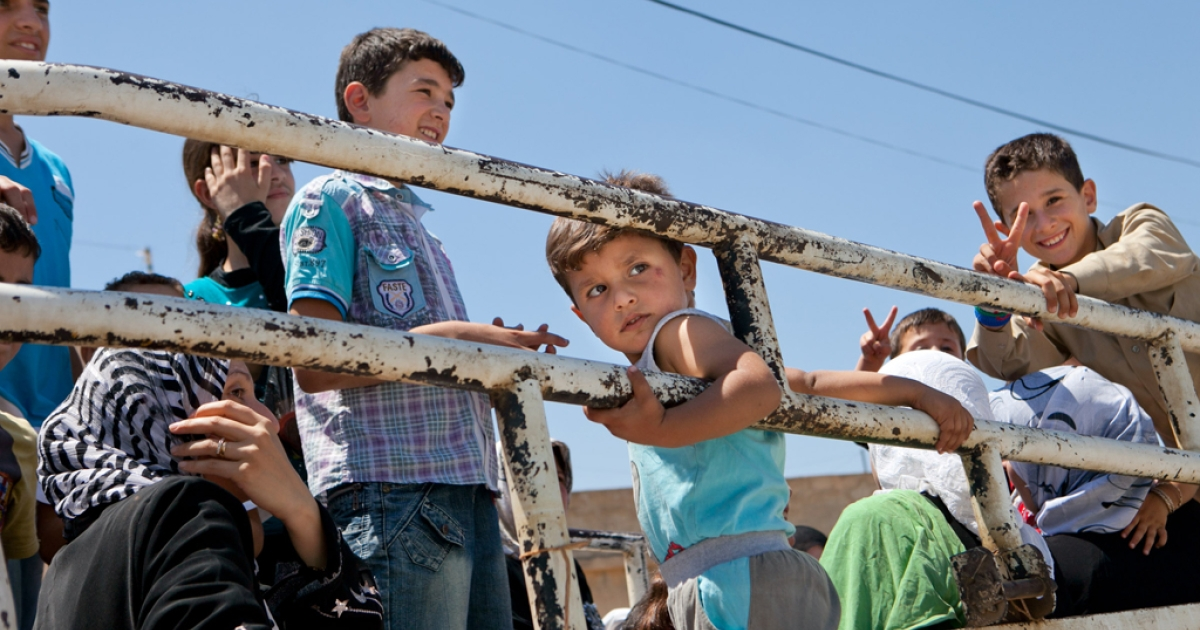 Syrian children ride in the back of a truck as they return to their village of Kfar Sijna on July 10, 2012, the day after it came under fire by Syrian government forces. The Red Cross has officially classified the Syrian conflict as a civil war, in order to hold combatants to international humanitarian law and the Geneva Conventions.</p>