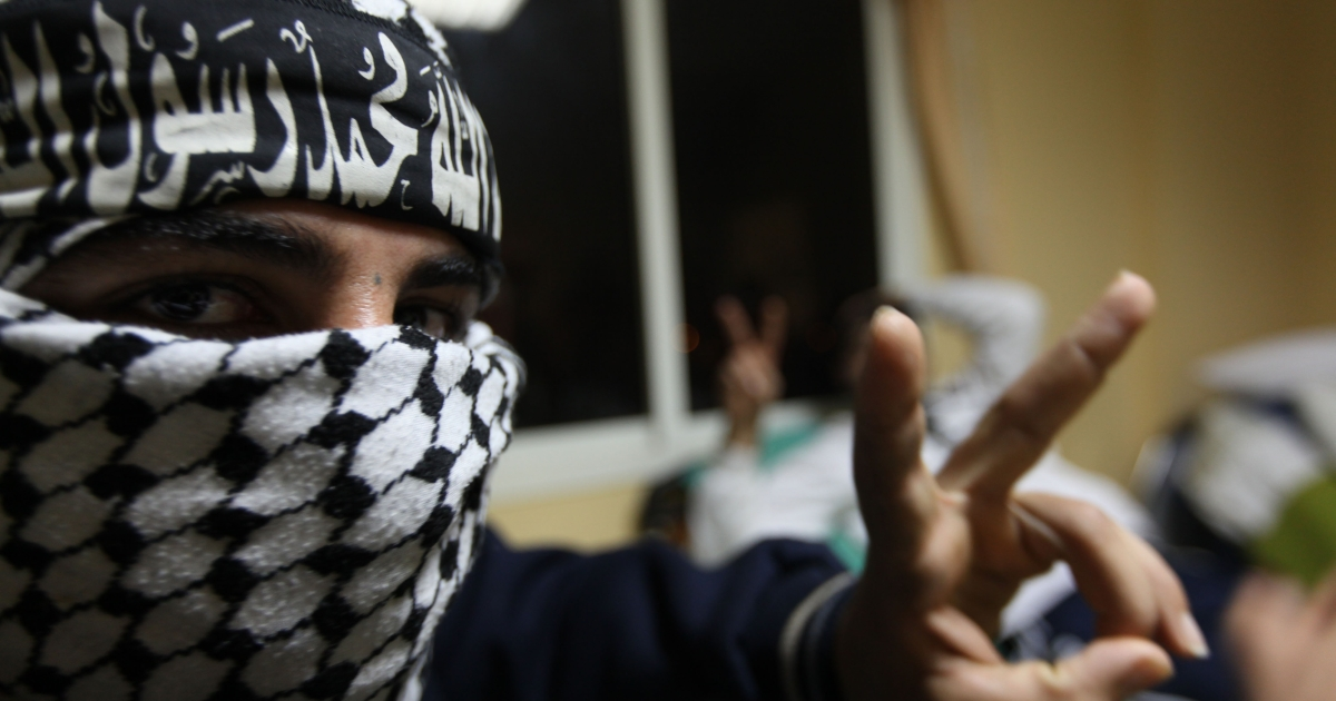A rebel wearing a chequered keffiyeh and a headband that reads in Arabic: 'There is no God but God, Mohammed is his messenger', flashes the V-sign for victory.</p>