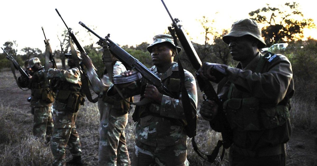 On July 19, 2011, soldiers from South African National Defense Force (SANDF) check their weapons before a night patrol in Kruger National Park (KNP). The military began patrolling KNP in April to combat a surge in rhino poaching. Around 21,000 rhinos, both black and white, remain in South Africa, home to 70 percent of the world's rhino population.</p>