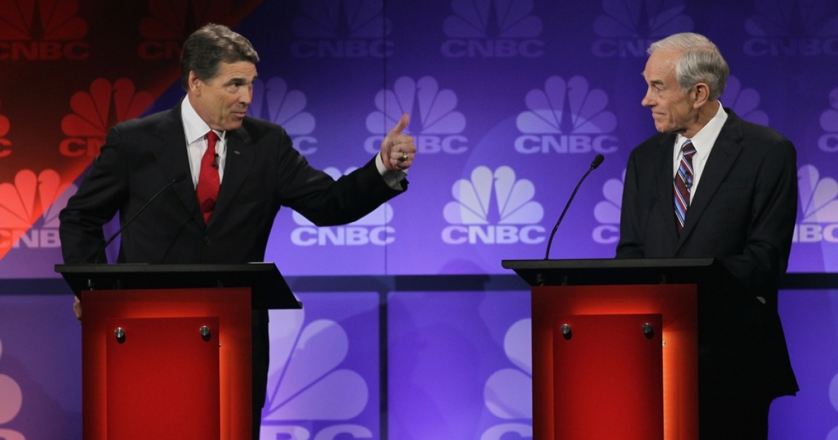 Republican presidential candidate Texas Governor Rick Perry (L) makes a point as U.S. Representative Ron Paul (R-TX), listens at a debate hosted by CNBC and the Michigan Republican Party at Oakland University on November 9, 2011 in Rochester, Michigan.</p>