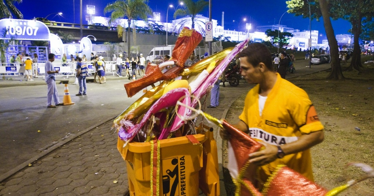 A garbage collector throws away fancy dresses abandoned by revellers after the last street band Carnival parades in downtown Rio de Janeiro on February 25, 2009.</p>