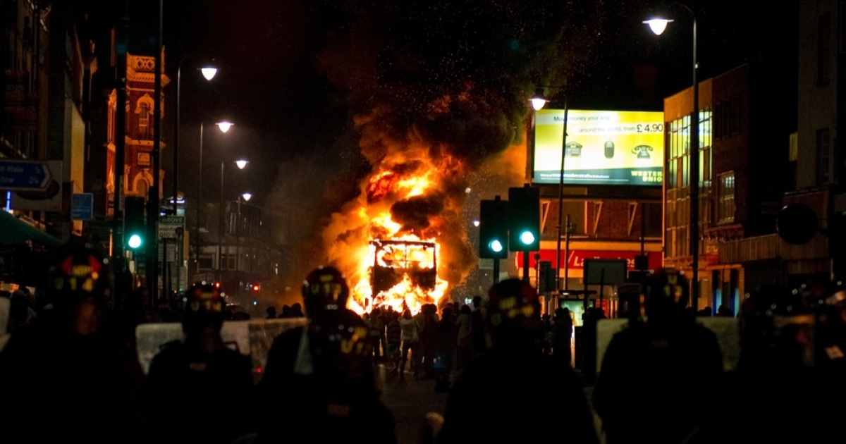 A double decker bus burns as riot police try to contain a large group of people on a main road in Tottenham, north London on August 6, 2011.</p>
