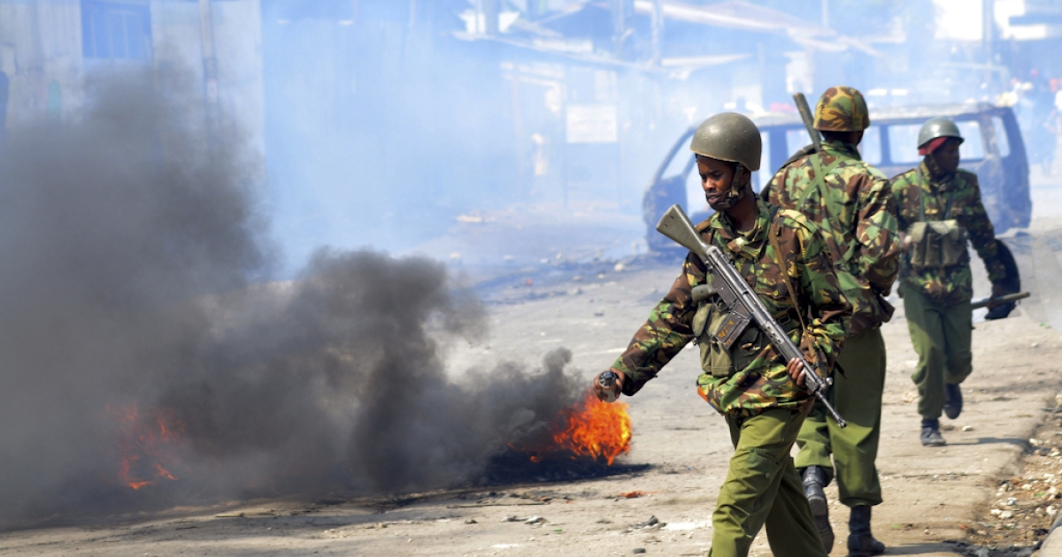 Kenyan paramilitary police walk past burning tyres in Kenya's port city of Mombasa during a second day of clashes after the killing of an extremist cleric linked to Al-Qaeda-allied Shabaab militants on August 28, 2012. Hundreds of angry youths have reportedly thrown stones, damaged cars after amassing in support of slain preacher Aboud Rogo Mohammed near the centre of Mombasa. The cleric, who was shot dead on August 27, 2012 by