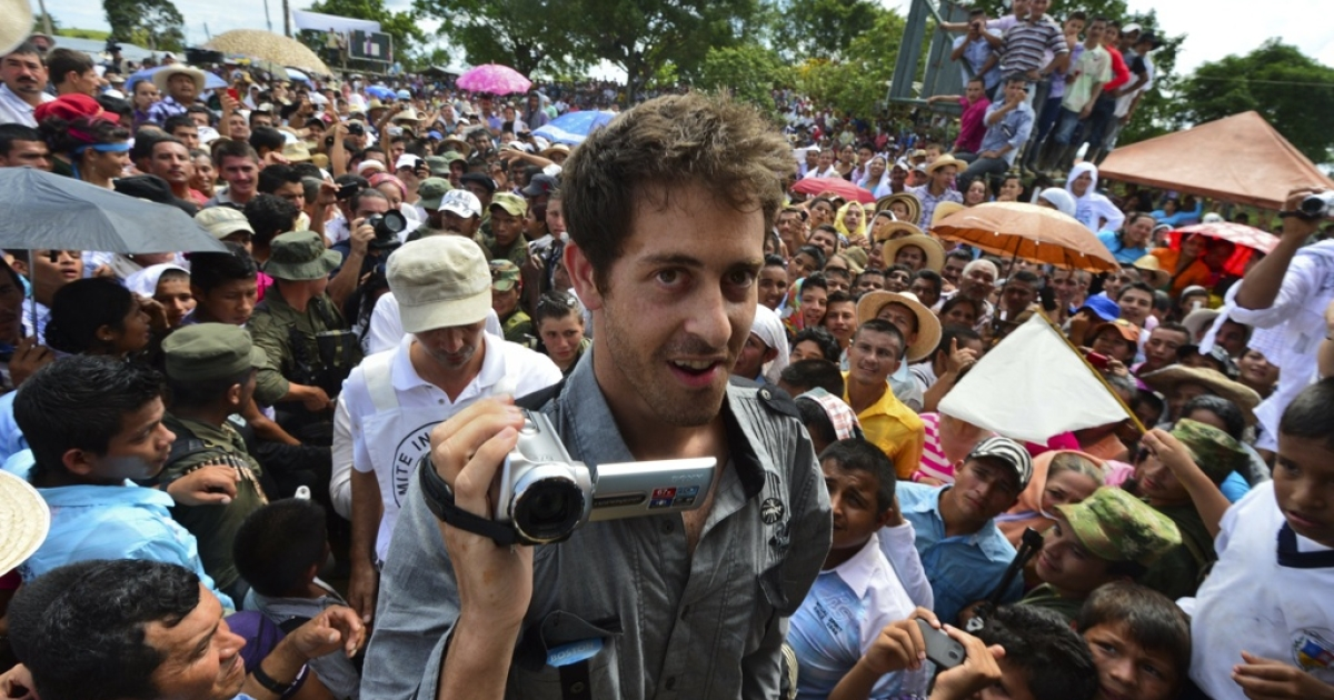 French journalist Romeo Langlois smiles and videos his hand-over from captivity by Colombia's FARC rebel group to a humanitarian commission on May 30, 2012 in the southern department of Caqueta.</p>