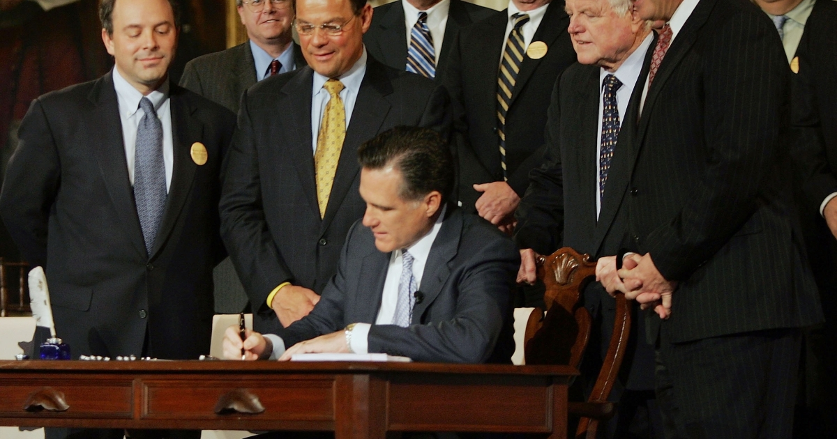 In this archival photo taken on April 12, 2006, Massachusetts Gov. Mitt Romney signs into law a healthcare reform bill that requires all state residents to have health insurance.</p>