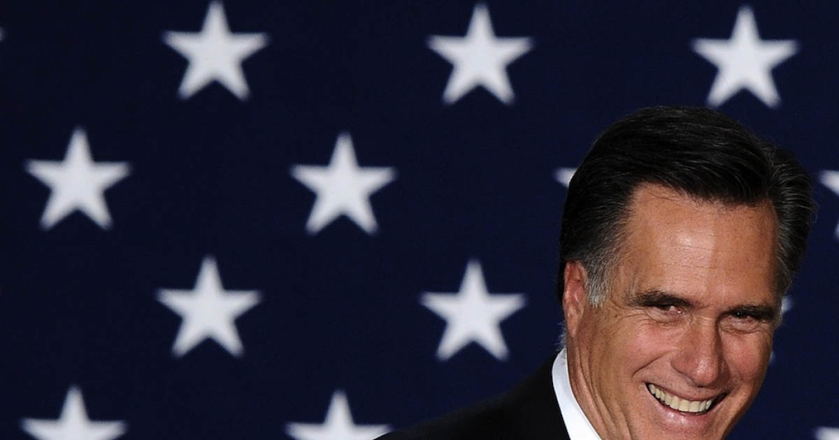 Republican presidential hopeful Mitt Romney smiles as he arrives to speaks at his caucus night rally following republican caucuses in Des Moines, Iowa, on January 3, 2012.</p>