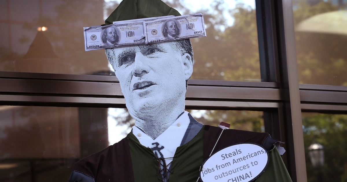 A protester carries a Mitt Romney puppet during a demonstration outside the offices of Bain Capital on Aug. 21, 2012 in Evanston, Illinois. The demonstrators were angry with Bain Capital's plans to move 165 jobs to China from the Sensata Technologies plant in Freeport, Illinois. Bain Capital purchased the Freeport plant two years ago.</p>