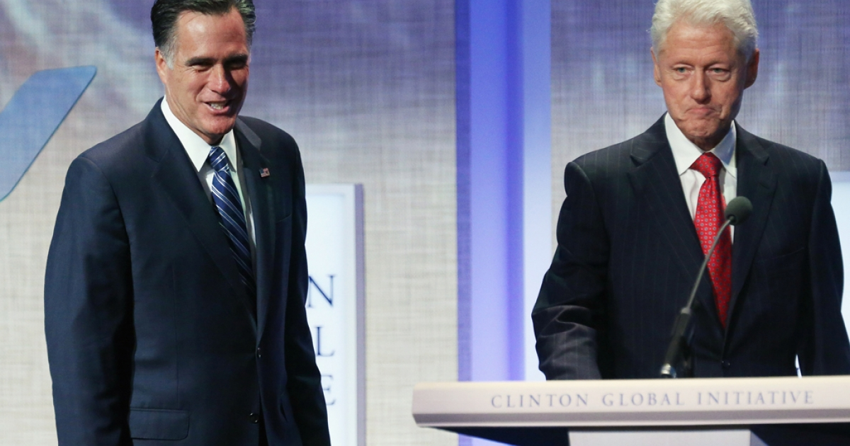 Former US President Bill Clinton walks to the podium with Republican presidential candidate, former Massachusetts Gov. Mitt Romney, at the Clinton Global Initiative meeting on September 25, 2012 in New York City.</p>