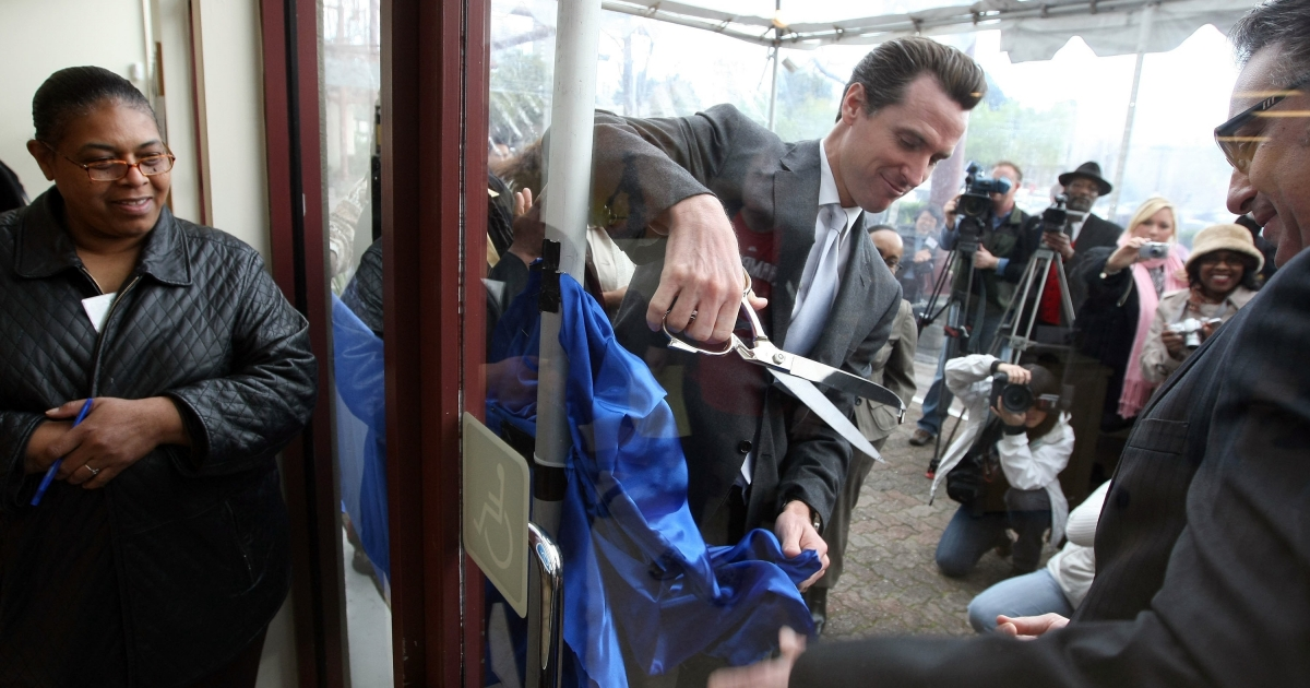 Ross Mirkarimi (R), then San Francisco supervisor, helps San Francisco mayor Gavin Newsom (C) cut a ribbon during the grand opening of the One-Stop Career Link Center in San Francisco on Feb. 25, 2009.</p>