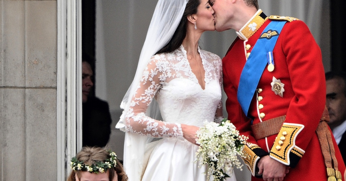 Britain's Prince William kisses his wife Kate, Duchess of Cambridge, on the balcony of Buckingham Palace, after their wedding service, on April 29, 2011, in London.</p>
