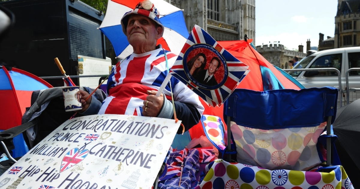 A man poses covered in royal memorabilia on the street in central London on April 27, 2011.</p>