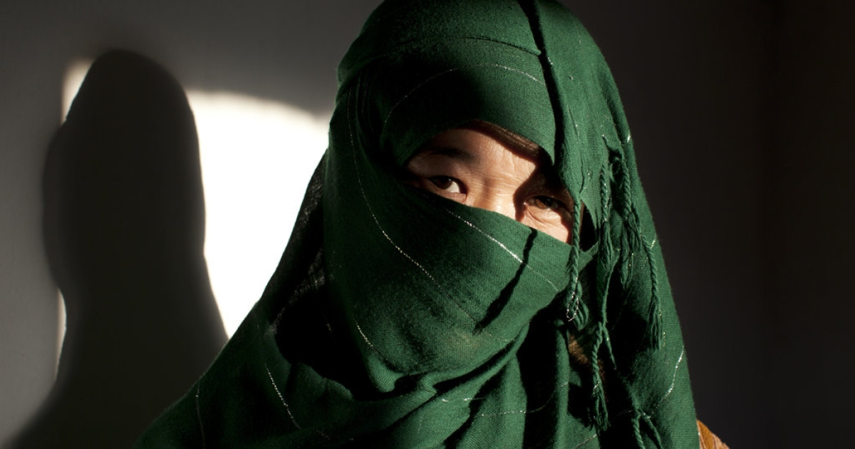 A battered 28-year-old Hazara woman hides behind her veil at a women's shelter October 8, 2010 in Bamiyan, Afghanistan. She came to the shelter after spending five months in prison. She was attempting to divorce her 50-year-old husband.</p>