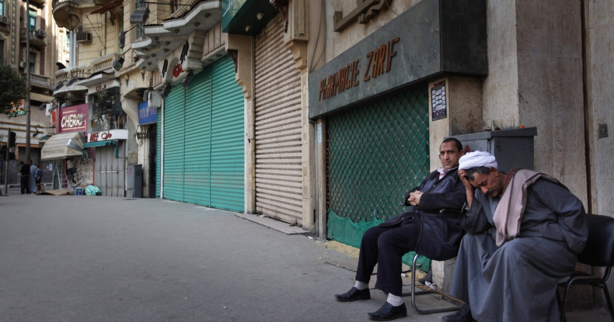 Local men sit next to closed shops on Jan. 31, 2011 in Cairo, Egypt. Most shops remain closed after more than two weeks of protests against the rule of President Hosni Mubarak.</p>