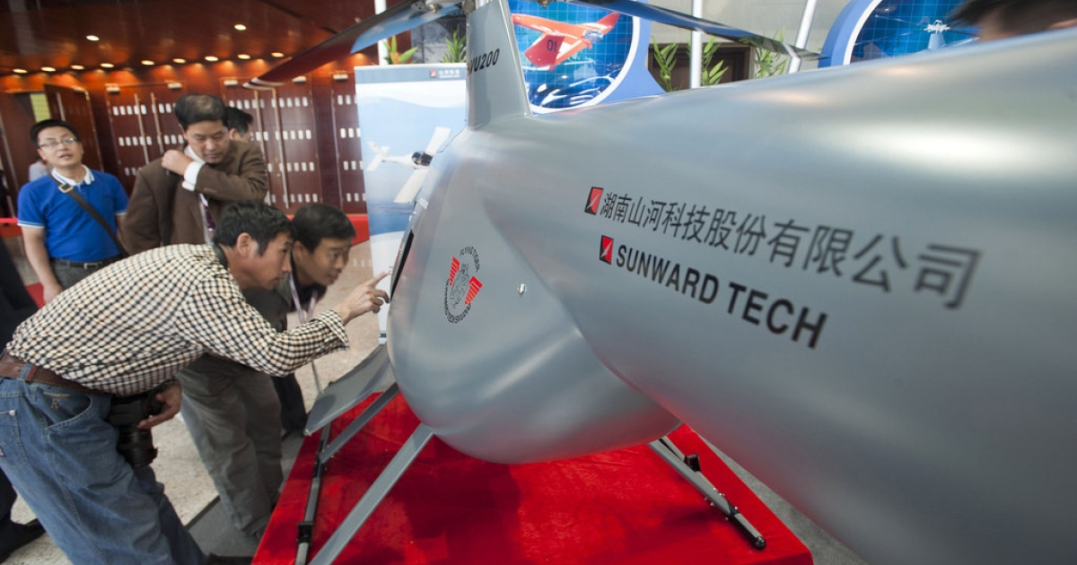 Chinese visitors examining an unmanned helicopter drone from a Chinese manufacturer at the China Aviation Expo in Beijing on September 21, 2011. Beijing on September 22 reacted furiously to a 5.85 billion USD deal to upgrade Taiwan's fleet of F-16 fighter jets, summoning the US ambassador to protest and warning the move would damage relations.</p>