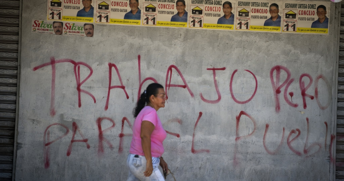 A woman passes by a wall with a graffiti that reads 'Work (yes), but for the people' in Puerto Gaitan, Meta department, eastern Colombia, on October 8, 2011.</p>